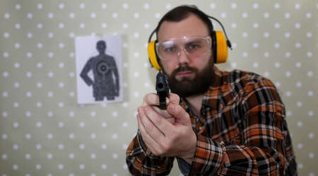 cowboy beard: man with put on protective goggles and ear training in pistol sh