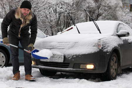 trapped: man cleans snow from a car on a winter morning