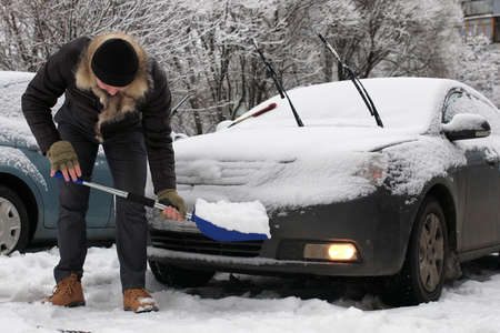man cleans snow from a car on a winter morning