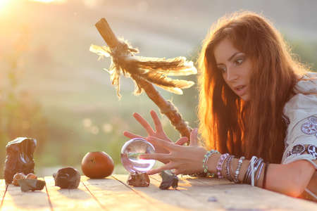 foretell: witch with crystal ball at sunset