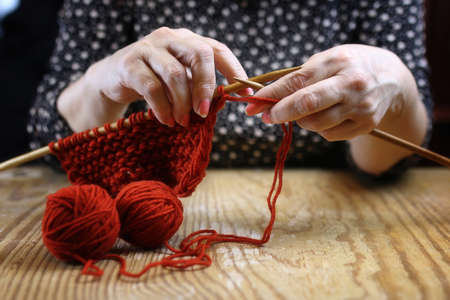 elderly woman is engaged in knitting warm sweaters for her grand