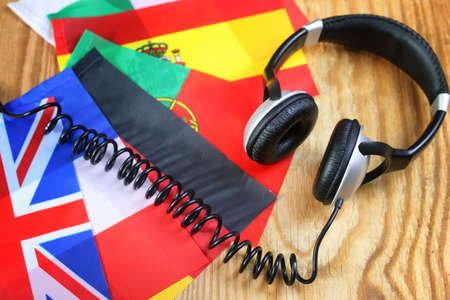 audio book: course language headphone and flag on a table