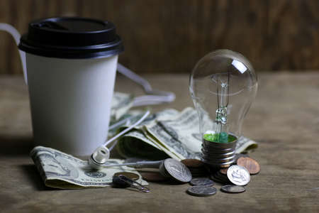 coins and crumpled money tungsten lamp filament Stock Photo