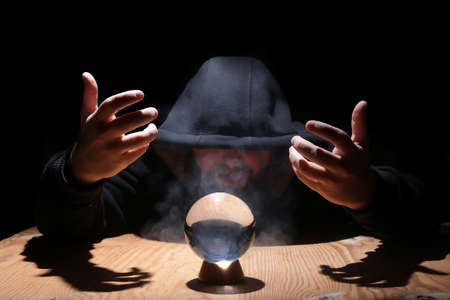 enchant: man in a black hood with cristal ball
