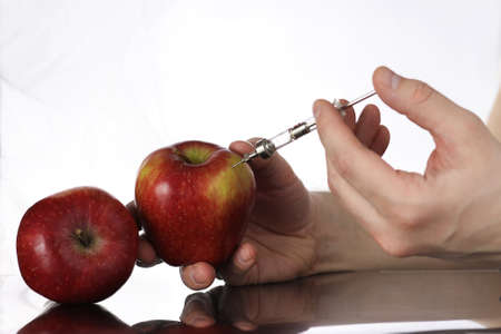 apple gmo: Genetically modified foods, apple pumped with chemicals Stock Photo