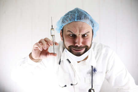 Crazy bearded doctor in a white coat and old syringe Stock Photo