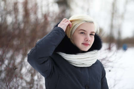 Young beautiful girl on a walk in winter park