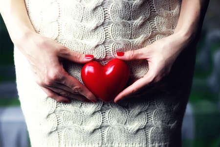 doctor holding gift: Woman holding heart Stock Photo