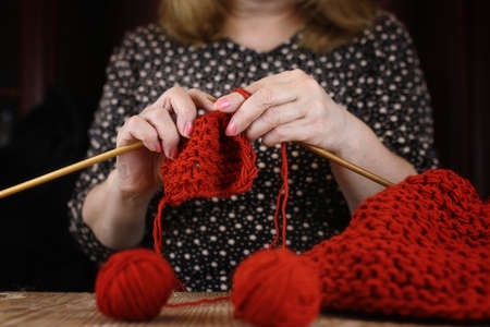 womans hand: elderly woman is engaged in knitting warm sweaters for her grand