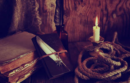 retro objects feather and leaher book with candle light
