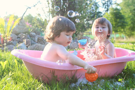 twins boy and girl in bath water outdoor Stock Photo