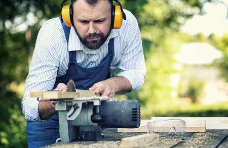 Worker beard man with circular saw Stock Photo