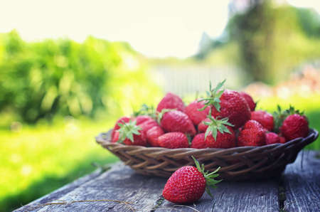 chessman: Strawberry in wicker plate on wooden background Stock Photo