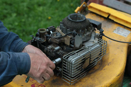 man with hands repairing a lawn mower engine Stock Photo