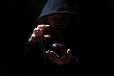 Man In A Black Hood With Cristal Ball Stock Photo, Picture And Royalty Free Image. Image 75750046.