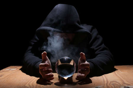 man in a black hood with cristal ball Banco de Imagens - 75674224