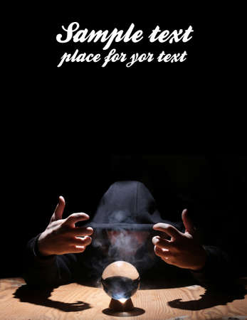 mystic place: man in a black hood with cristal ball and empty space for text