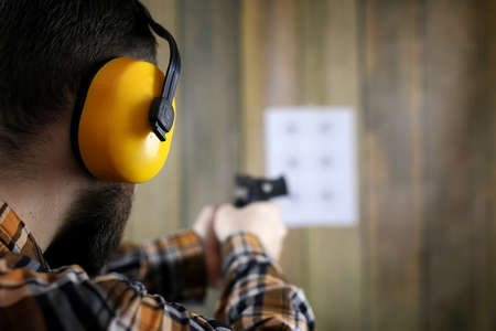 man with put on protective goggles and ear training in shooting gun range