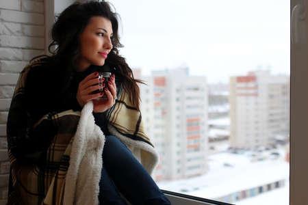 beautiful girl waiting for love sitting on the windowsill wrappe Standard-Bild