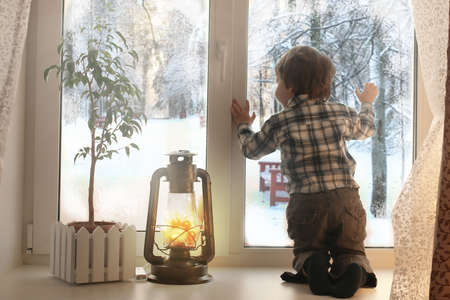 boy sitting on a white window sill and looks out the window