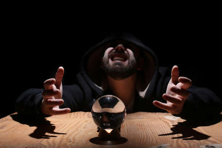 Man in a black hood with crystal ball