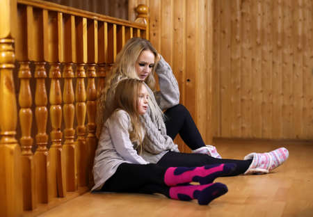 parent with child sitting on the floor near the wooden railing