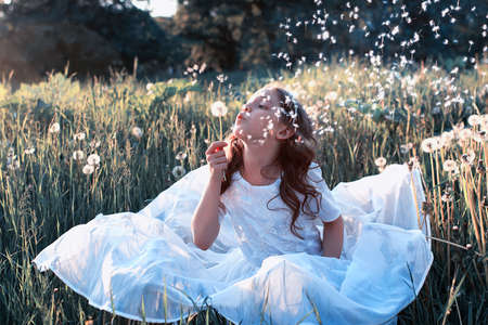 Teen girl blowing seeds from a flower dandelion in spring park Banque d'images
