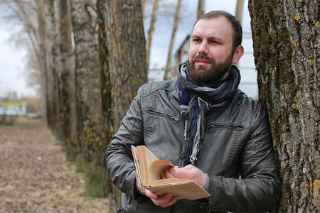 man read book tree park