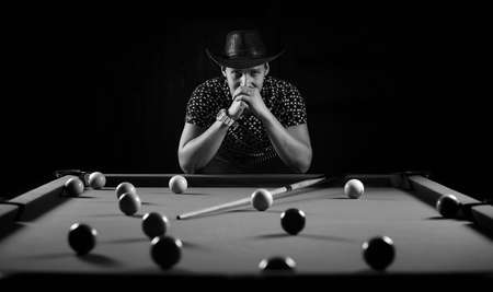 snooker halls: monochrome photo young man playing billiards