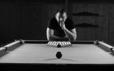 snooker hall: monochrome photo young man playing billiards