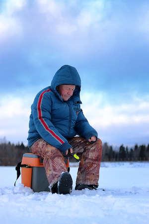 blue fish: Winter season old man fishing on lake