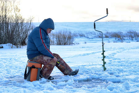 blue fish: elderly man fishing in the winter on the lake