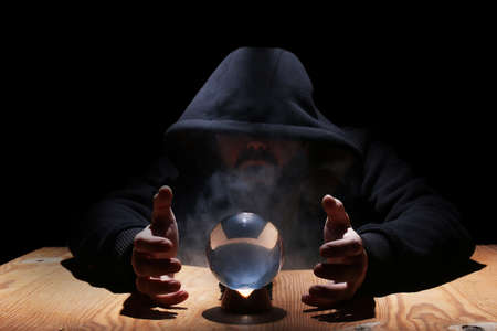 man in a black hood with cristal ball summon evil Imagens