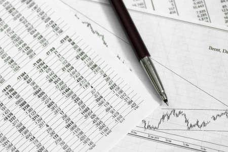 pen op papier met de prijsopgaven en geeft een overzicht van de dynamiek van hun veranderingen en munten