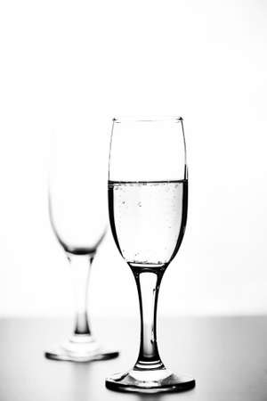 glass of champagne on white table on a white background isolate