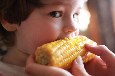 little boy eats greedily biting corn