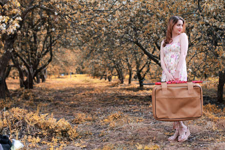 skirts: girl with leather suitcase for travel in the autumn park on walk