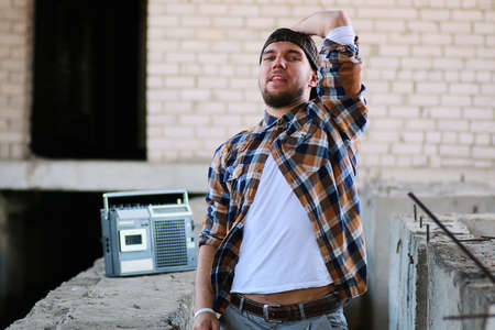 A man dressed in hip hop style poses