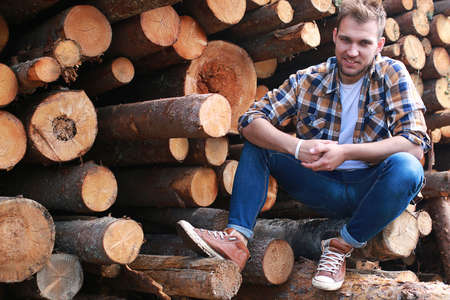 A man at the factory processing wood, sawing logs Stock Photo