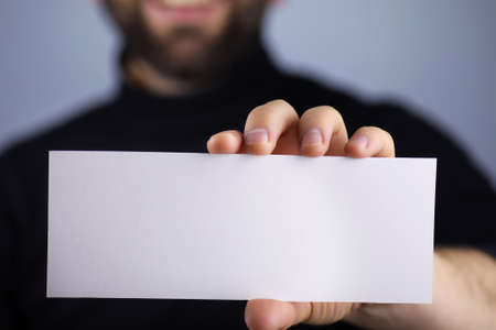 note booklet: a small white piece of paper in his hand man