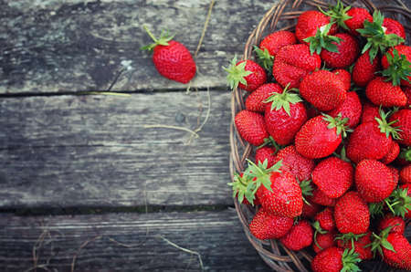 Strawberry in wicker plate on wooden background Stock Photo