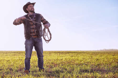 Cowboy standing in a field at sunset