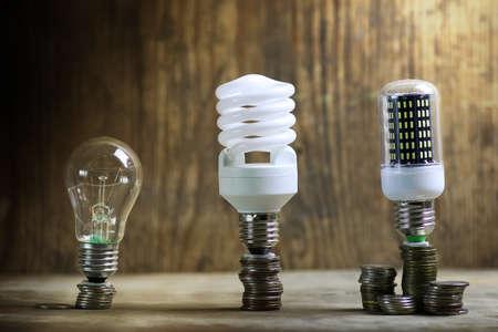 Verschiedene Lampe auf Münzeinsparungen Konzept Standard-Bild - 87415738