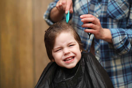 A little boy is trimmed in the hairdressers bright emotions on his face Stock Photo