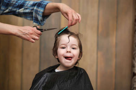 A little boy is trimmed in the hairdressers bright emotions on