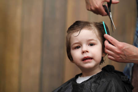 salon background: A little boy is trimmed in the hairdressers bright emotions on