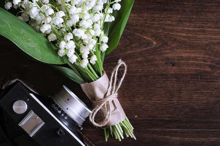 Kytice mladých lilie z údolí na dřevěném stole