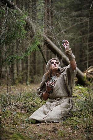 sotana: Un hombre en una sotana pasa un ritual en un bosque oscuro con una bola de cristal y un libro