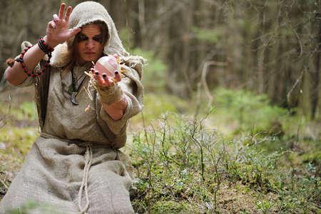 eye ball: A man in a cassock spends a ritual in a dark forest