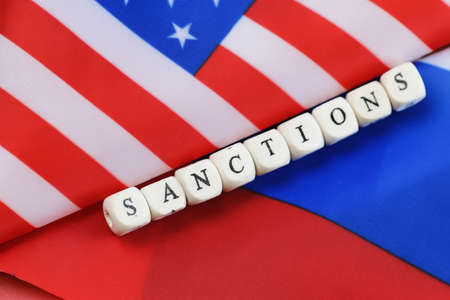 politic: russian usa flag sanctions wooden letters on them